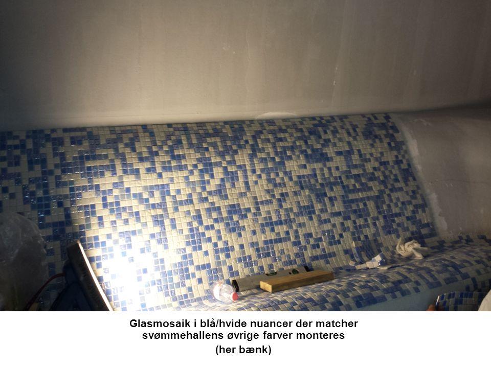 Glasmosaik i blå/hvide nuancer der matcher svømmehallens øvrige farver monteres