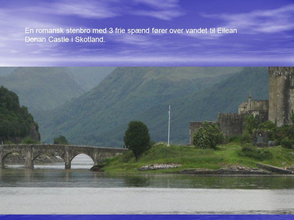 En romansk stenbro med 3 frie spænd fører over vandet til Eilean Donan Castle i Skotland.